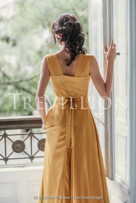 Nikaa BRUNETTE WOMAN IN YELLOW DRESS WATCHING BY BALCONY Women