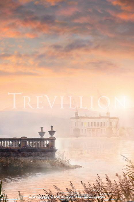 Lee Avison stately home seen across a misty lake at sunset