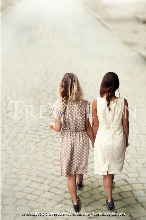 Svetoslava Madarova TWO GIRLS HOLDING HANDS ON COBBLED STREET Women