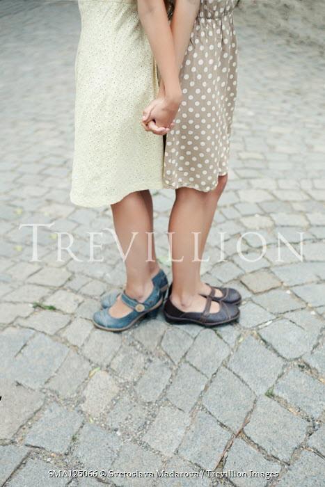 Svetoslava Madarova TWO GIRLS HOLDING HANDS BACK TO BACK OUTDOORS Women