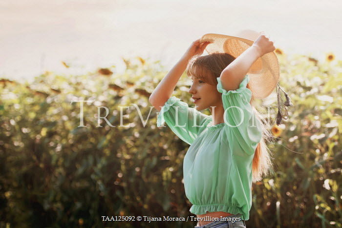 Tijana Moraca GIRL HOLDING STRAW HAT IN SUNFLOWER FIELD Women