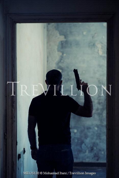 Mohamad Itani MAN STANDING IN DERELICT BUILDING WITH GUN Men