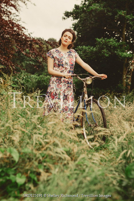 Shelley Richmond WOMAN IN FLORAL DRESS WITH BICYCLE IN COUNTRYSIDE Women