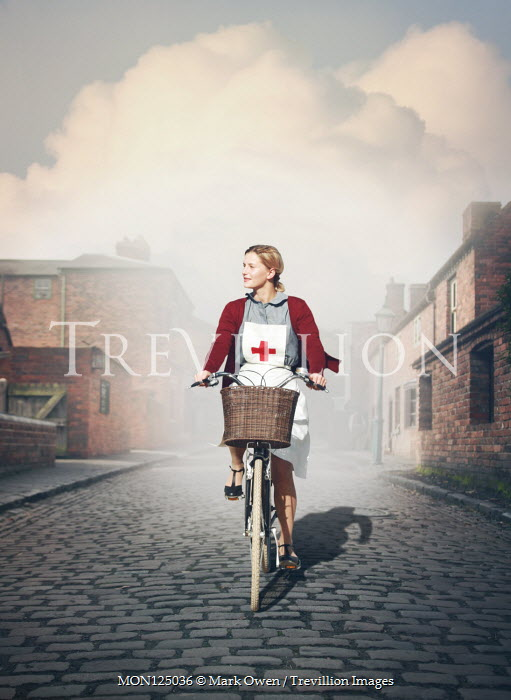 Mark Owen NURSE RIDING BIKE ON COBBLED STREET Women