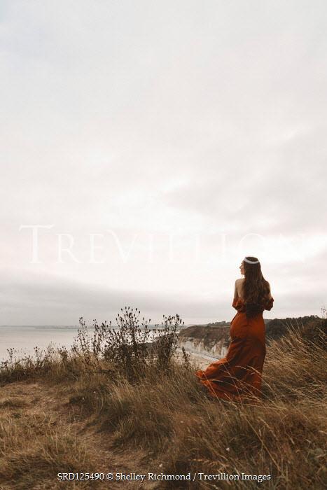 Shelley Richmond BRUNETTE WOMAN IN GOWN STANDING BY SEA CLIFFS Women