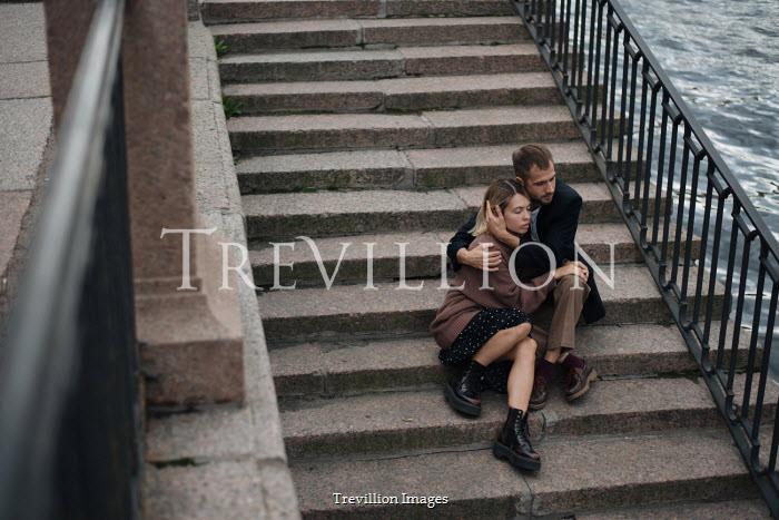 Alina Zhidovinova HUGGING COUPLE SITTING ON STEPS BY RIVER Couples