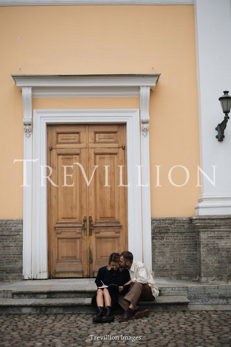 Alina Zhidovinova MAN KISSING WOMAN ON STEPS SITTING OUTSIDE BUILDING Couples