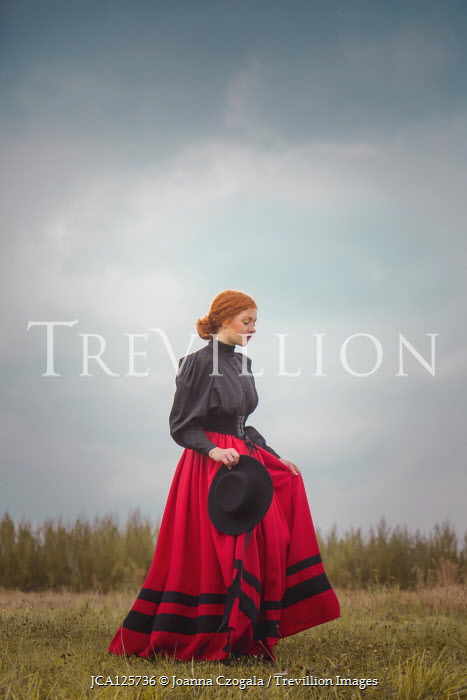 Joanna Czogala HISTORICAL WOMAN WITH RED HAIR HOLDING HAT IN COUNTRYSIDE Women