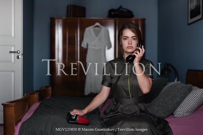 Maxim Guselnikov WOMAN HOLDING TELEPHONE SITTING ON BED Women
