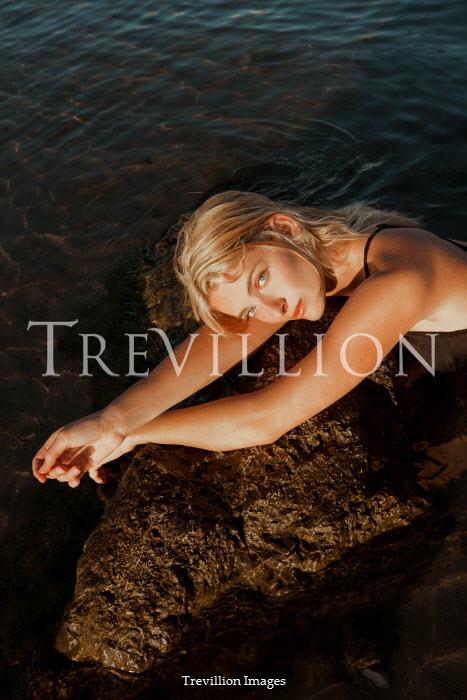 Greta Larosa BLONDE WOMAN IN SEA LYING ON ROCK Women