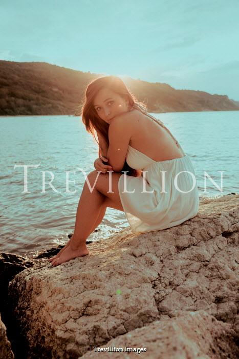 Greta Larosa BRUNETTE WOMAN SITTING ON ROCK BY SEA Women