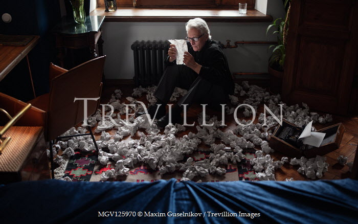 Maxim Guselnikov MAN SITTING READING WITH BALLS OF PAPER ON FLOOR Old People