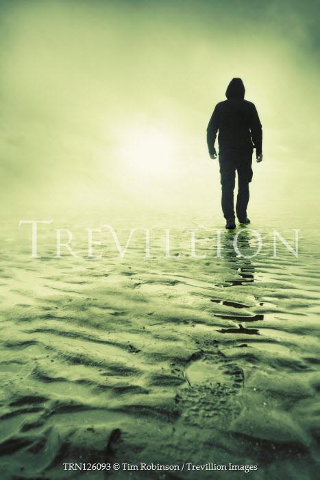 Tim Robinson SILHOUETTED MAN IN HOOD WALKING IN BEACH Men
