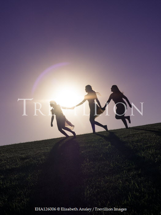 Elisabeth Ansley THREE FEMALES RUNNING HOLDING HANDS OUTDOORS Groups/Crowds