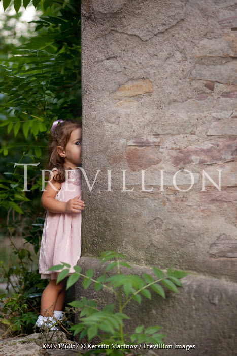 Kerstin Marinov LITTLE GIRL OUTDOORS HIDING BY STONE WALL Children