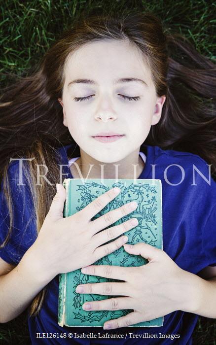 Isabelle Lafrance LITTLE GIRL LYING ON GRASS HOLDING BOOK Children