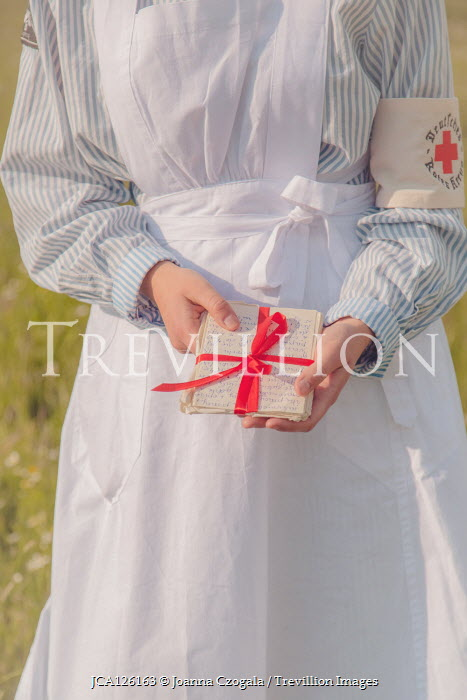 Joanna Czogala WARTIME NURSE HOLDING LETTERS TIED WITH RED RIBBON Women