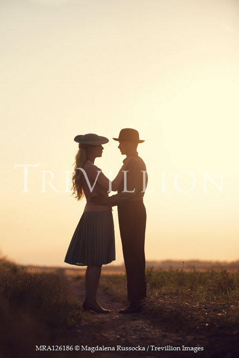 Magdalena Russocka RETRO COUPLE EMBRACING IN FIELD AT SUNSET Couples
