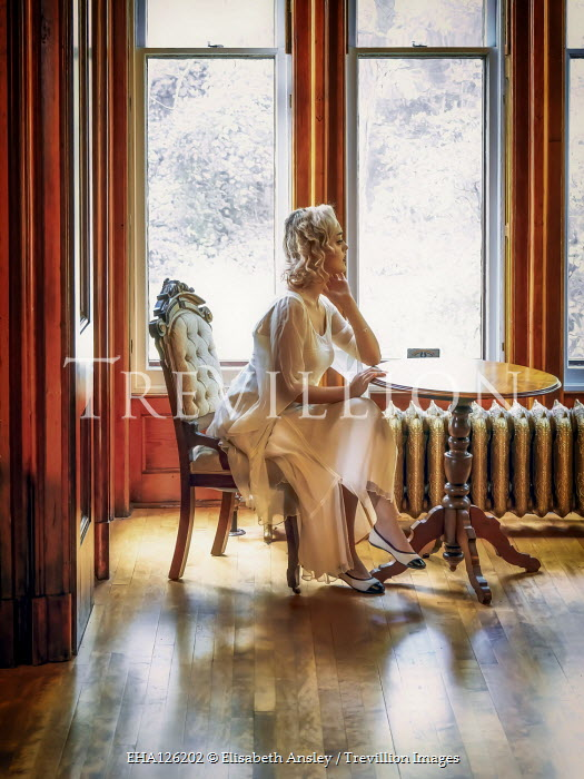 Elisabeth Ansley BLONDE WOMAN SITTING BY WINDOW IN LARGE HOUSE Women