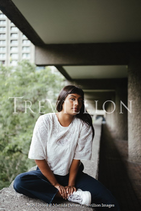 Matilda Delves ASIAN WOMAN SITTING BY MODERN BUILDING Women