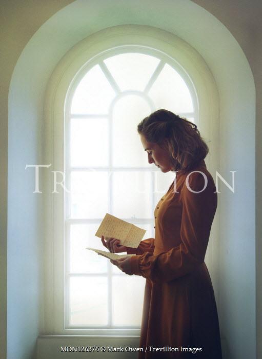 Mark Owen WOMAN STANDING READING LETTER INDOORS BY WINDOW Women