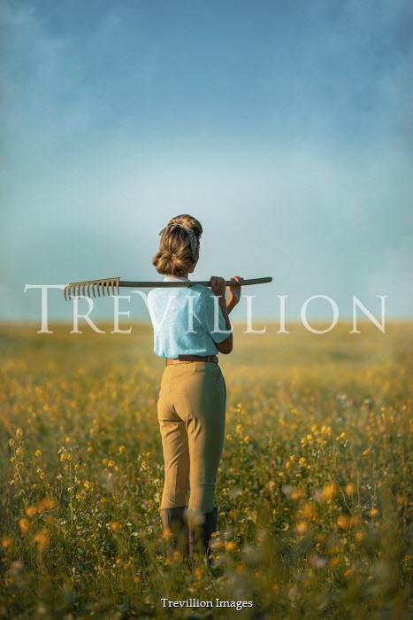Ildiko Neer Land girl with rake on shoulder standing in rape field