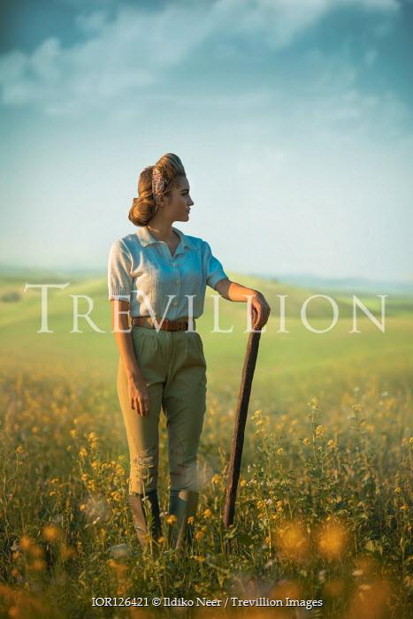 Ildiko Neer Land girl leaning on pitchfork in rape field