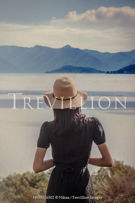 Nikaa WOMAN IN HAT WATCHING LAKE AND MOUNTAINS Women