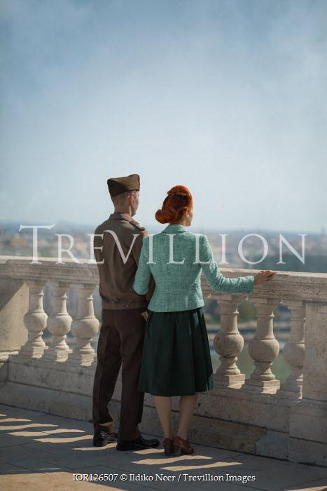 Ildiko Neer Wartime couple standing on balcony watching town Couples