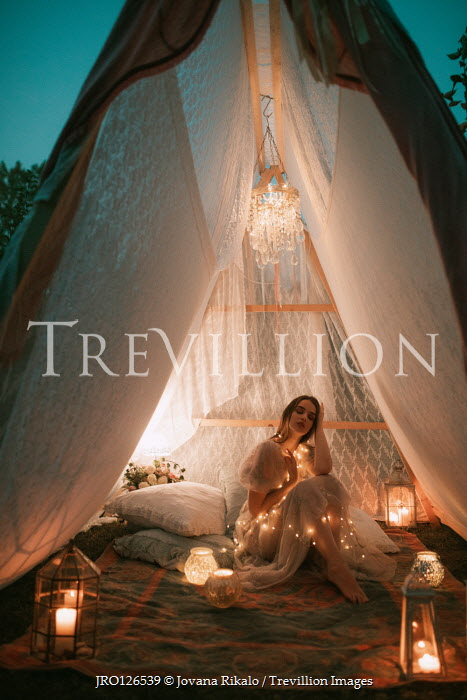 Jovana Rikalo GIRL SITTING IN TENT WITH LIGHTS AND CANDLES Women