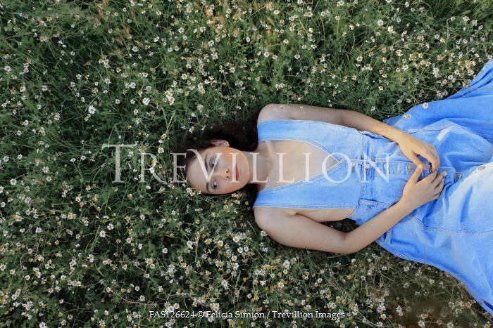 Felicia Simion GIRL IN DENIM DRESS LYING IN FIELD WITH DAISIES Women