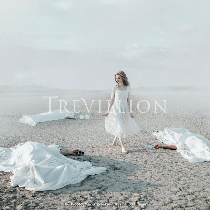 Jovana Rikalo WOMAN ON BEACH WITH THREE PEOPLE LYING UNDER SHEETS Groups/Crowds
