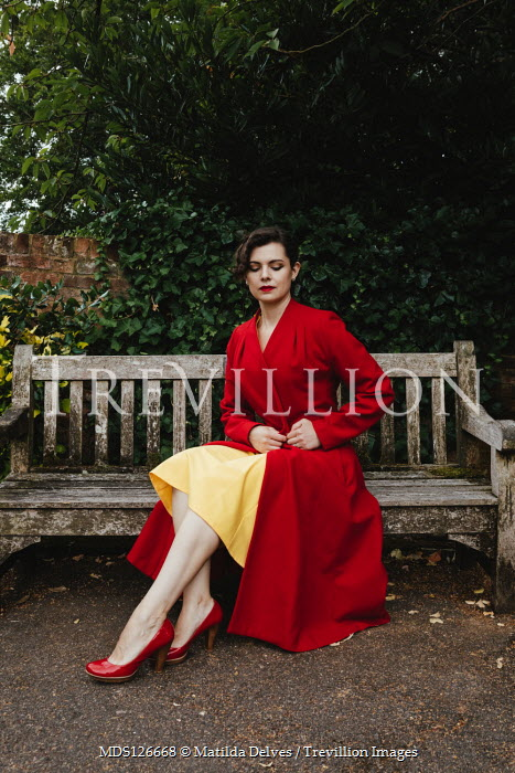 Matilda Delves WOMAN IN RED COAT SITTING ON BENCH OUTDOORS Women