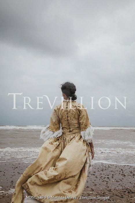 Matilda Delves HISTORICAL WOMAN STANDING ON WINDY BEACH Women
