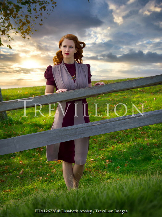 Elisabeth Ansley RETRO WOMAN WITH RED HAIR BY FENCE IN FIELD Women