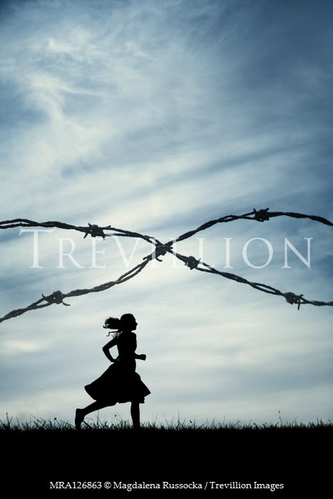 Magdalena Russocka SILHOUETTED GIRL RUNNING IN FIELD WITH BARBED WIRE Women