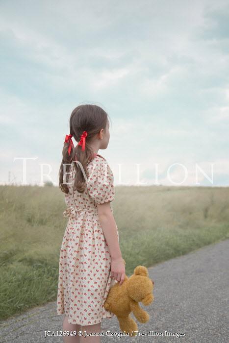 Joanna Czogala Girl with teddy bear on rural road