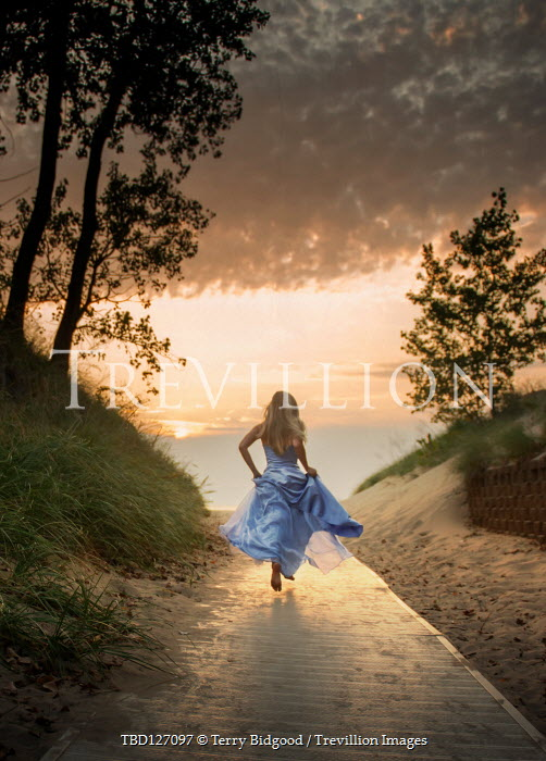 Terry Bidgood Young woman in blue dress running on boardwalk during sunset