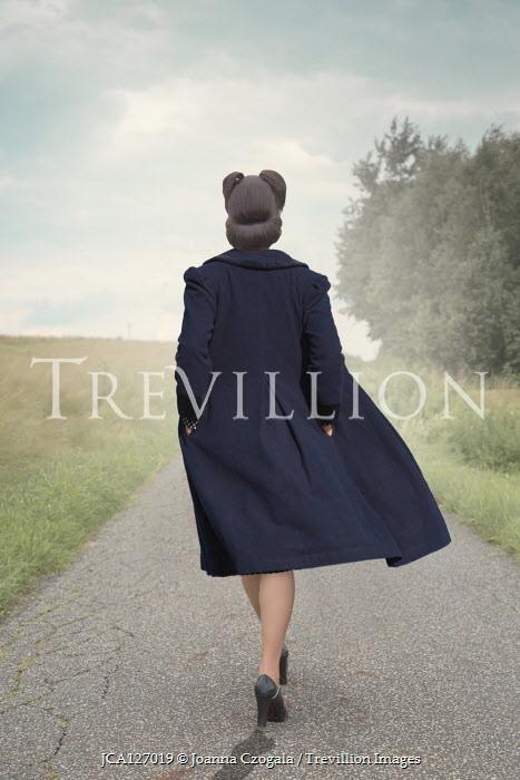 Joanna Czogala Woman in blue coat walking on rural road