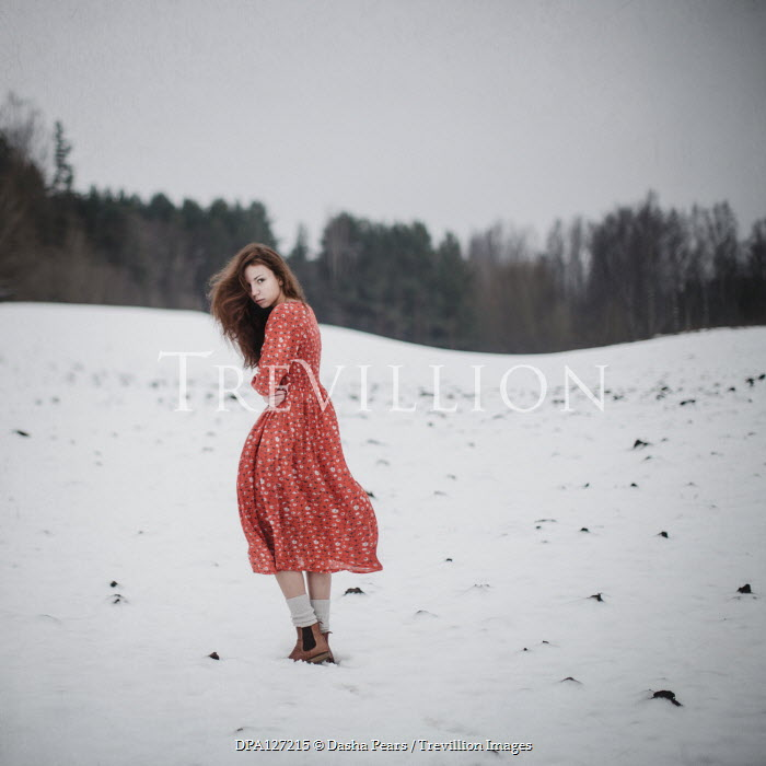 Dasha Pears Young woman in red dress standing in snow