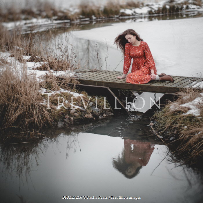 Dasha Pears Young woman in red dress sitting on bridge during winter