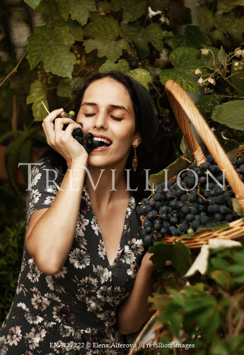 Elena Alferova Young woman eating grapes from vine