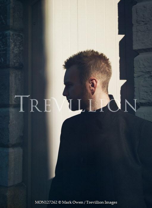 Mark Owen Man in black coat in shadow