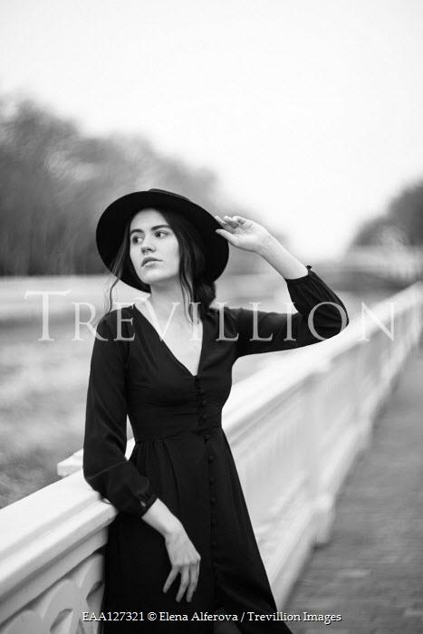 Elena Alferova WOMAN IN HAT LEANING ON WALL OUTDOORS Women