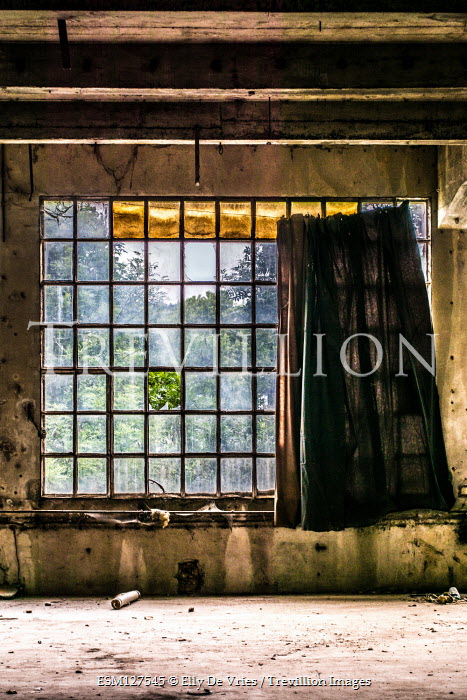 Elly De Vries Window with curtain in abandoned building