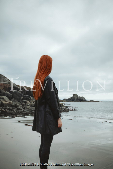 Shelley Richmond Young woman in black coat standing on beach