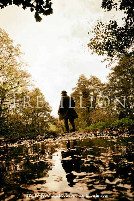 Tim Robinson Man in coat walking by puddle in forest