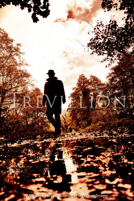 Tim Robinson Silhouette of man in hat and coat by puddle in forest