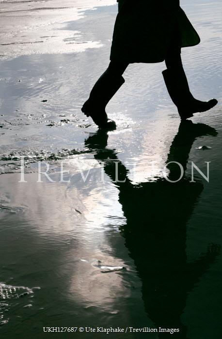 Ute Klaphake Silhouette of legs of man in boots walking on beach