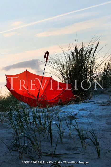 Ute Klaphake Red umbrella on sand dune at sunset